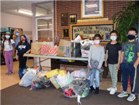 Barnum Woods students with bags of shoes to be donated in the front lobby of the school building.  thumbnail183231